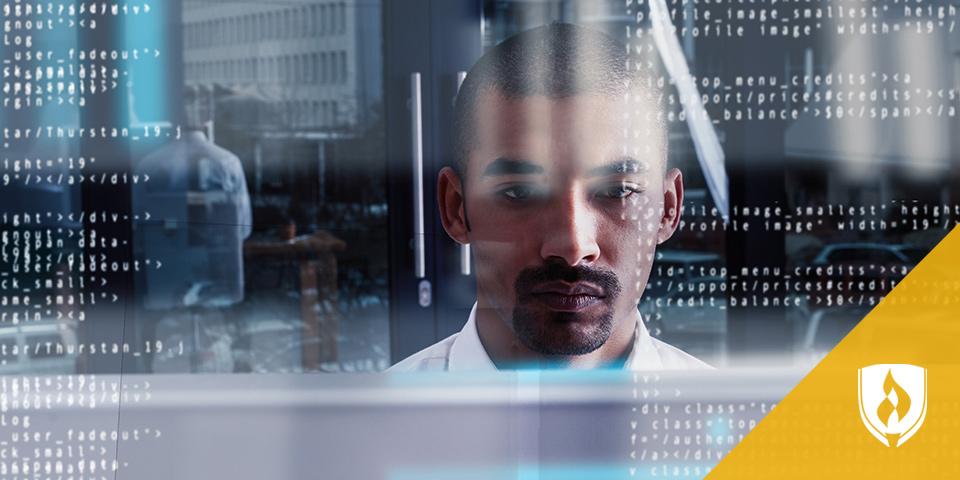 man sitting in front of computer looking at information on screen
