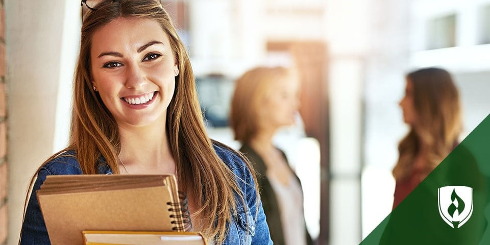 female student smiling holding books with students in background