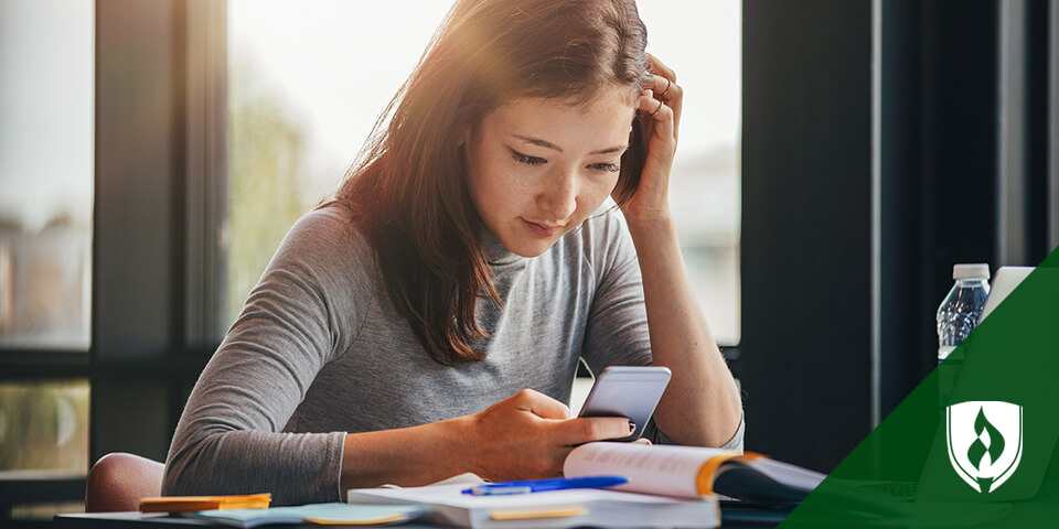 female student looking at smartphone while studying