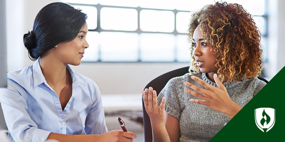 two female professionals talking in conference room