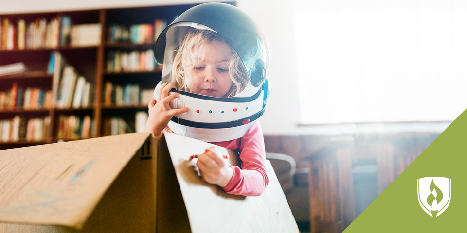 young girl playing astronaut in a box