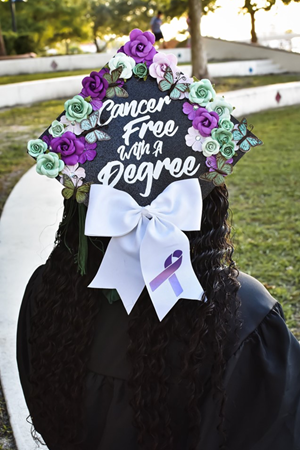 Graduation cap with 'Cancer Free With A Degree' written on it surrounded by flowers.