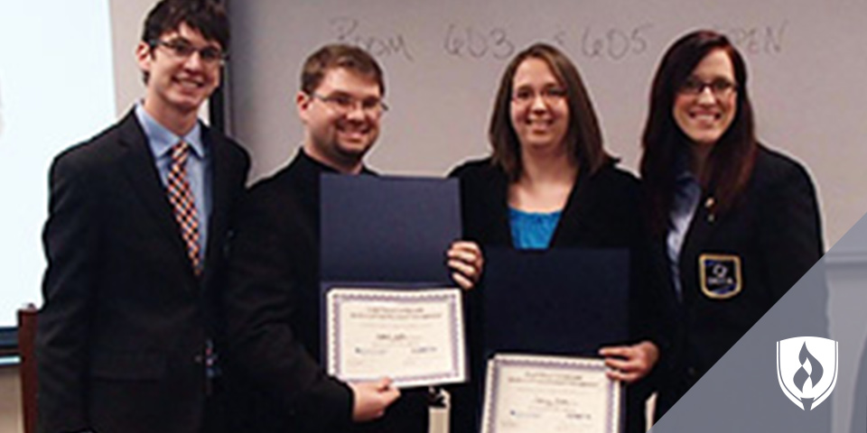 two business management students with certificates