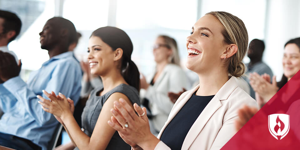 business woman sitting in conference room clapping