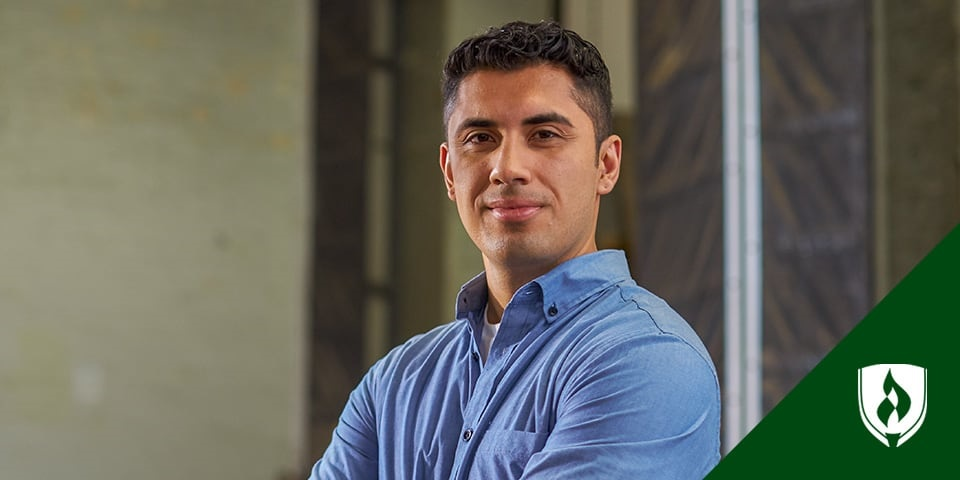 man holding a tablet with semi-trucks in background