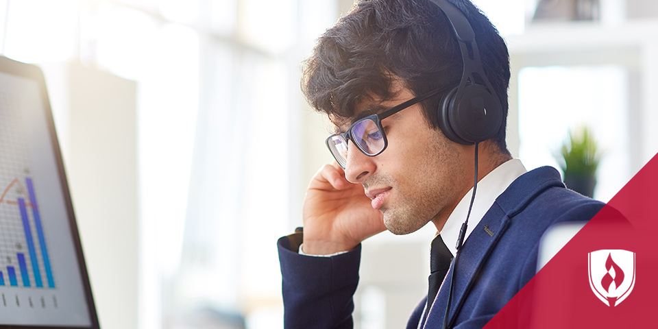 man with headphones in front of monitor