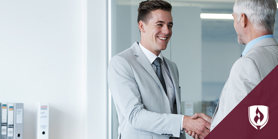 young business man shaking hands with older business man