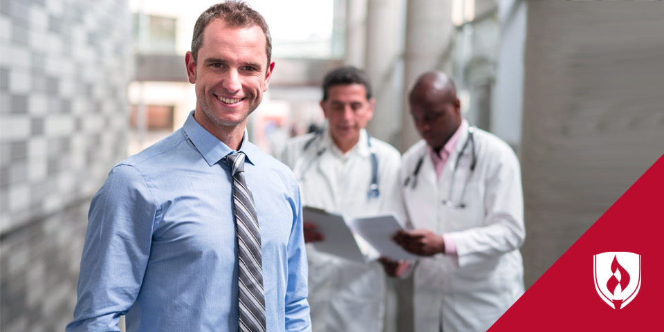 man in tie standing with health technicians in background