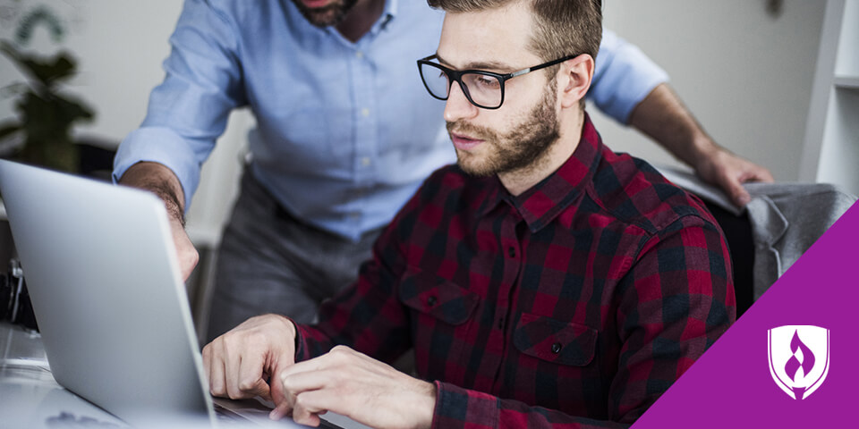 man working on laptop with senior designer giving direction