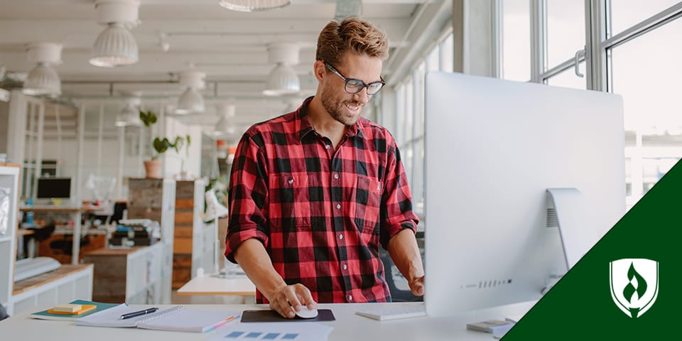 male designer standing at desk working on computer