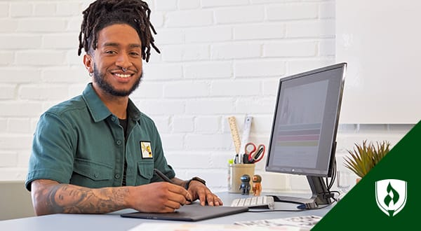 Young man smiling and working at a desktop computer