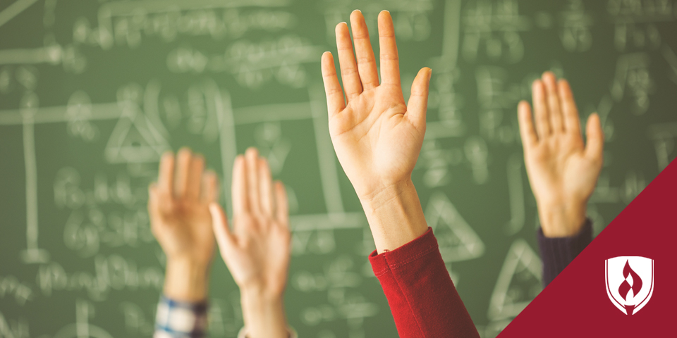 Raised hands in front of a chalkboard