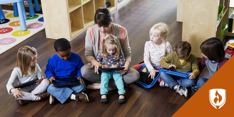 female teacher working with young children on tablets