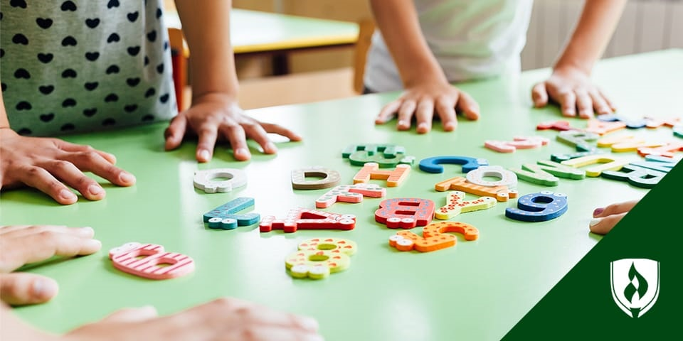 photo of preschoolers playing with letters