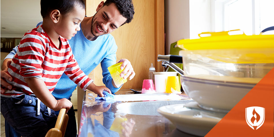 father and child washing dishes