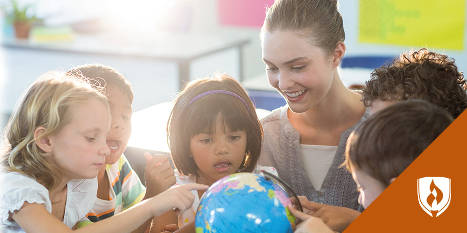 female teacher showing children world globe