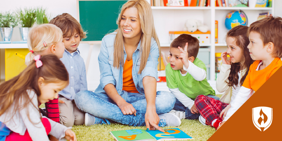 daycare provider sitting on floor talking to young children