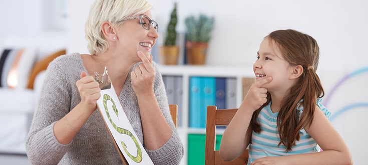 woman doing speech lessons with young girl