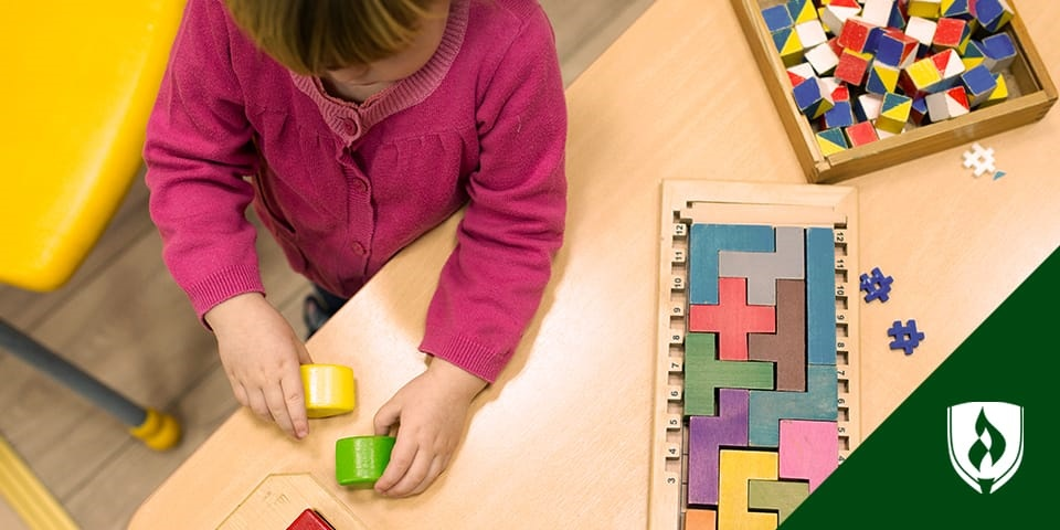 girl playing with blocks at table