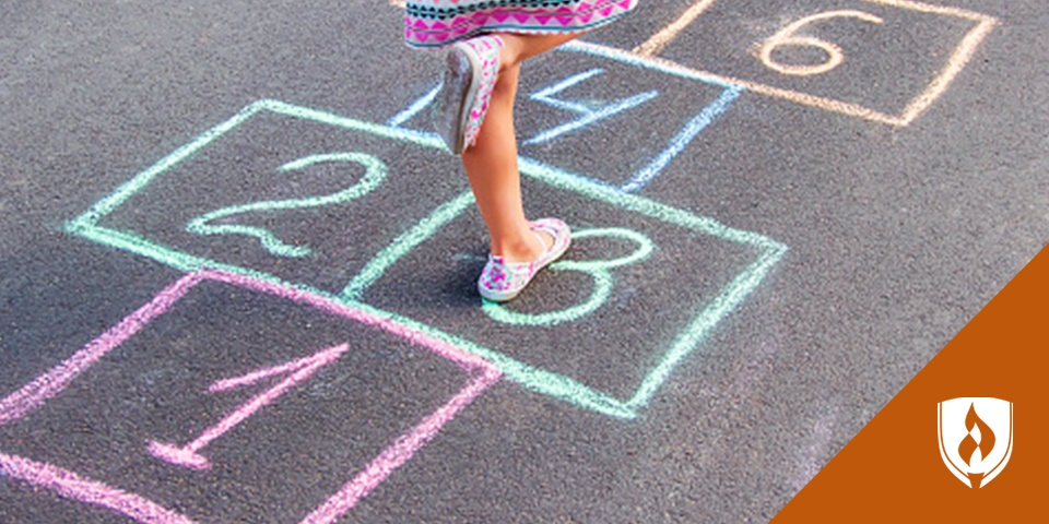 Photograph of a preschooler playing hopscotch to help them learn math skills
