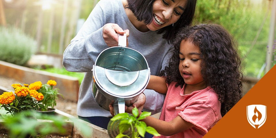 mom and daughter watering plants together outdoors
