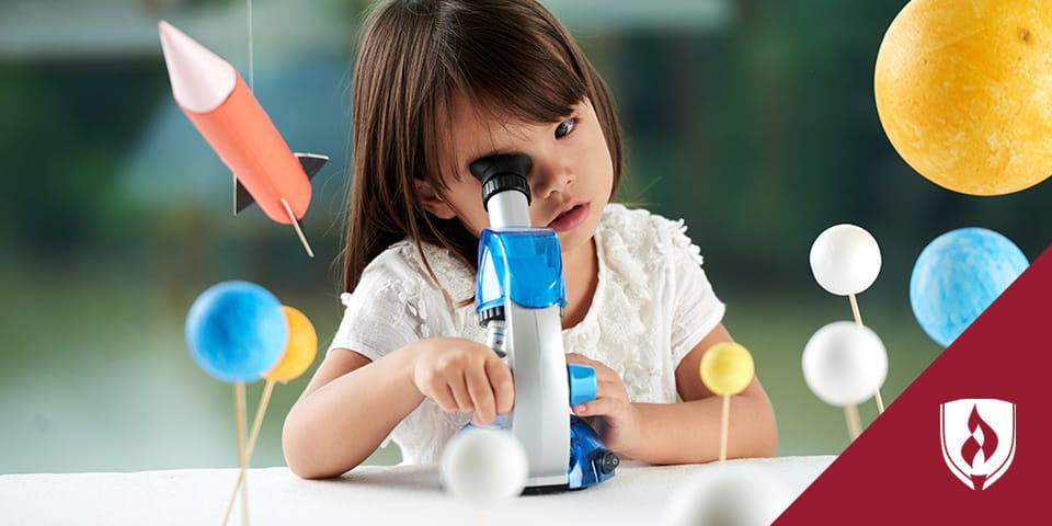 child looking in microscope