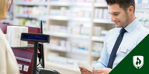 male pharmacy technician helping customer at checkout