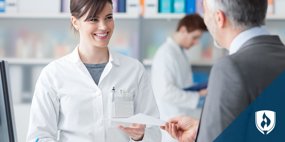 female pharmacy technician handing out slips