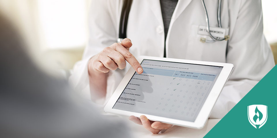 medical professional showing information on a tablet to a patient