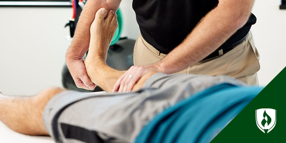 physical therapy assistant hold patient knee over foam roller