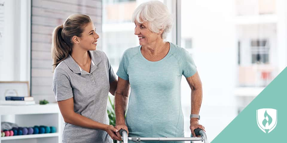 physical therapist assistant helping elderly patient