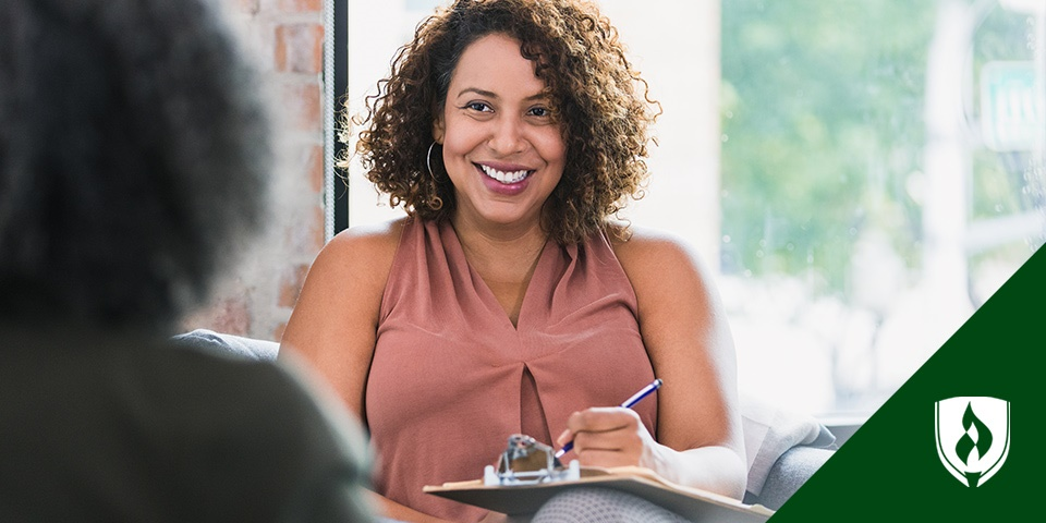 photo of a human services professional smiling at a client and writing on a clipboard