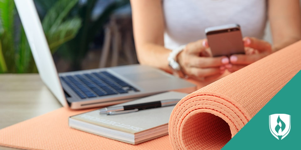 open laptop next to rolled up yoga mat