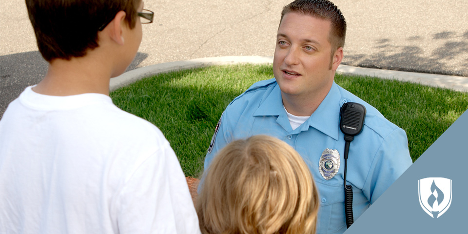 male police officer talking to young children