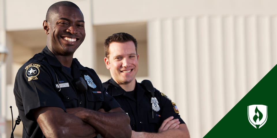Two smiling police officers with their arms crossed.