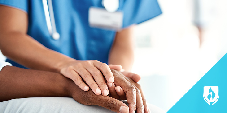 female nurse holding patients hand