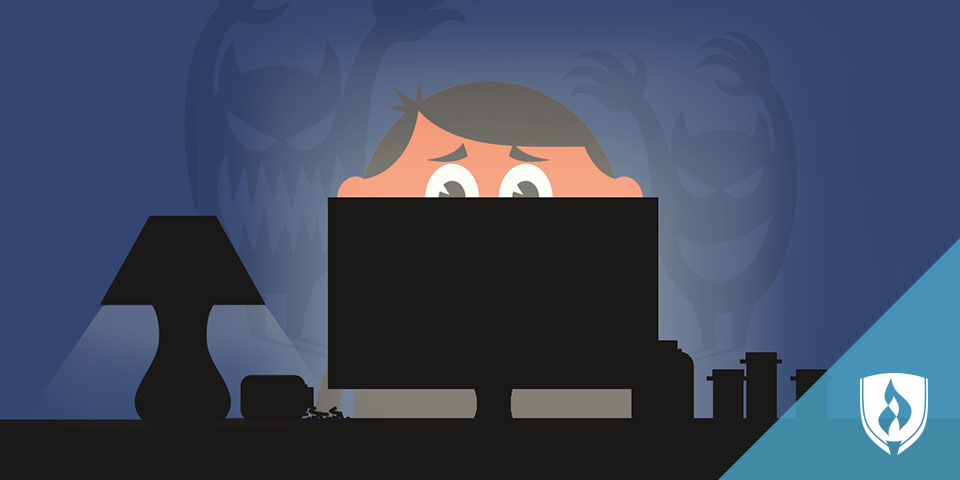 illustrated man looking at computer with monsters behind him