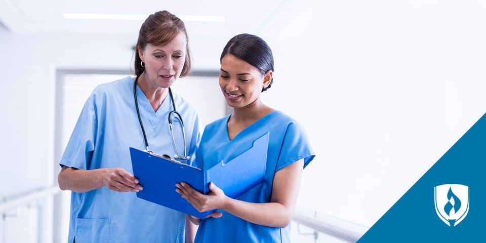 two female nurses looking at a chart