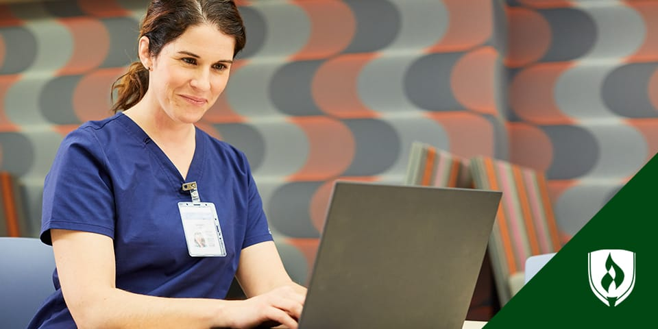 woman in scrubs working on laptop