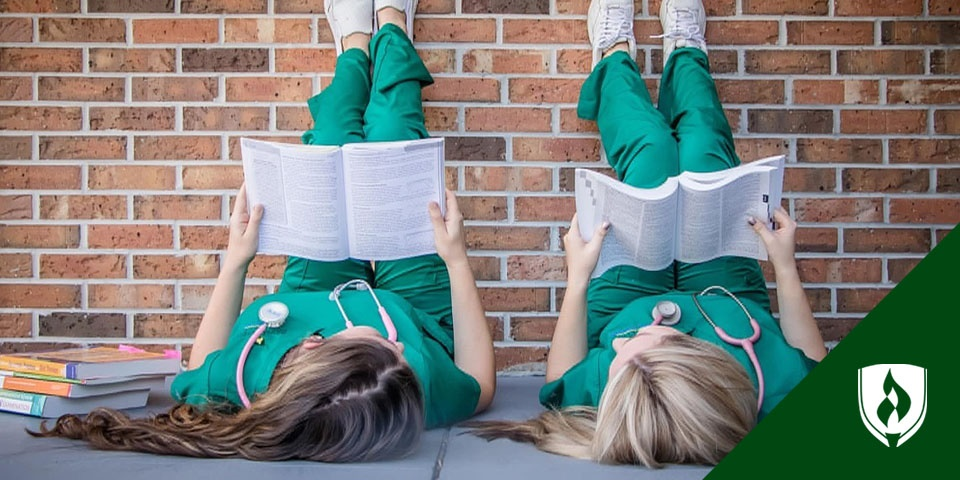 photo of two nurses reading textbooks lying on the sidewalk with their feet up on a brick wall