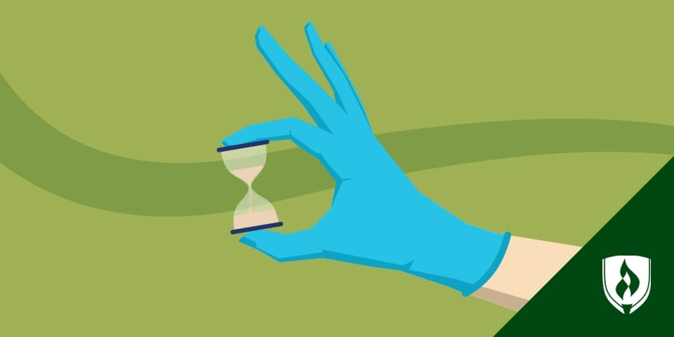 A nurse's hand with a disposable glove holding an hourglass