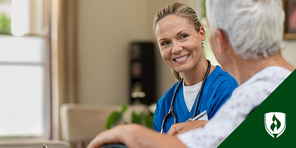 Blonde female nurse smiling and talking to elderly patient.