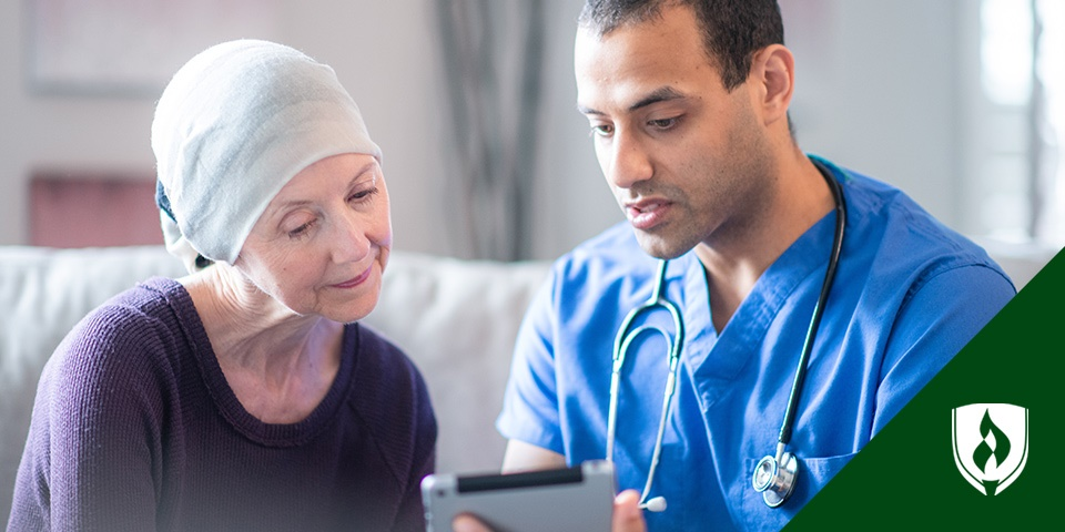 Photo of an oncology nurse helping a patient read information on a tablet