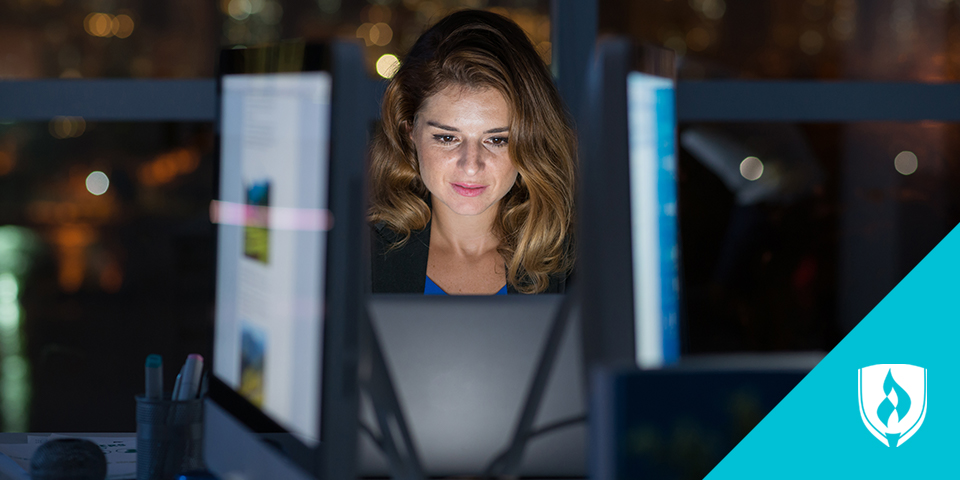 Woman working on a computer at night