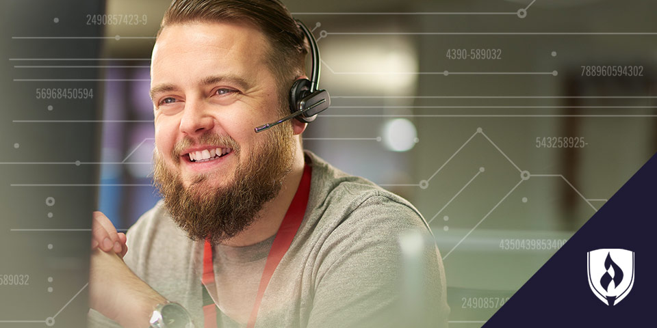 bearded male sitting with phone headset looking at computer screen