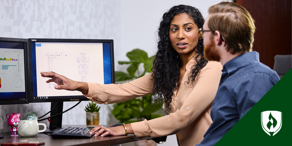 woman working at computer with man