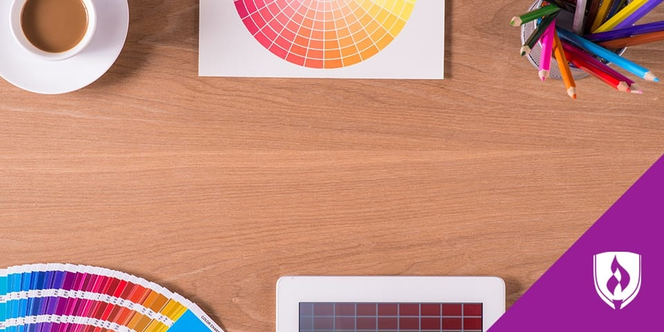 photo of a desk with colored pencils, color wheel, and a coffee