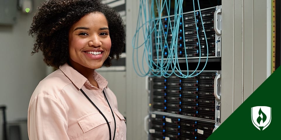 A female network administrator standing in front of a server cluster